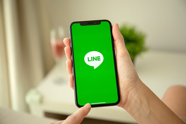 Woman hand holding iPhone X with social networking service Line